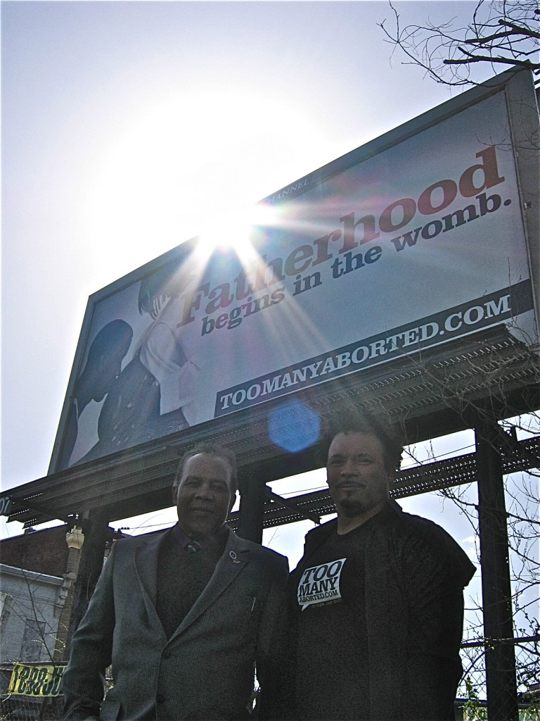 "Jimmie Hollis, of Project Courageous in New Jersey, and Ryan Bomberger of The Radiance Foundation stand beneath a ""Fatherhood Begins in the Womb"" billboard, just down the street from Planned Parenthood."